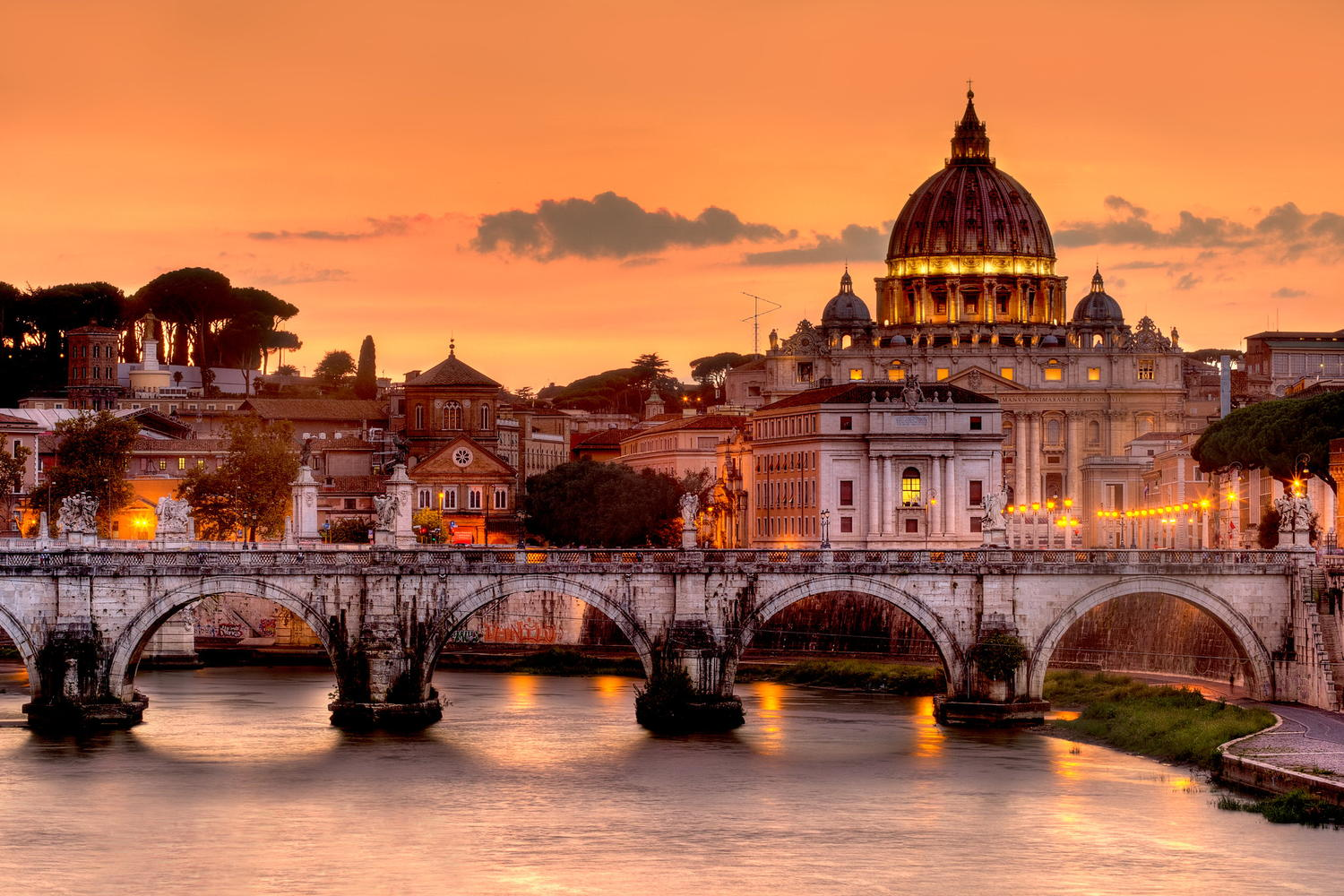 St. Peter Basilica in Vatican city and Sant'Angelo bridge over Tiber river in Rome, Italy.