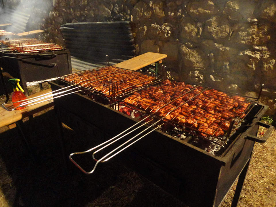 Aromatic chunks of pork are flame grilled on huge fires set outside the castle square